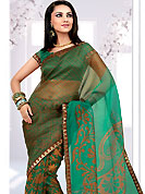 Try out this year top trends, glowing, bold and natural collection. This pastel green and mustard net printed casual wear saree have beautiful floral and butti print work on all over. Border has amazing contrasting fabric lace. It's cool and has a very modern look to impress all. Matching blouse is available.  Slight Color variations are possible due to differing screen and photograph resolutions.