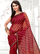 Exquisite combination of color, fabric can be seen here. This red net printed casual wear saree have beautiful floral, dots and leheriya print work on all over. Border has amazing contrasting fabric lace. It's cool and has a very modern look to impress all. Matching blouse is available.  Slight Color variations are possible due to differing screen and photograph resolutions.
