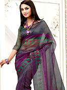 The most radiant carnival of style and beauty. This purple net printed casual wear saree have beautiful zigzag and butti print work on all over. Border has amazing contrasting fabric lace. It's cool and has a very modern look to impress all. Matching blouse is available.  Slight Color variations are possible due to differing screen and photograph resolutions.