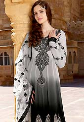 Breathtaking collection of designer suits with stylish embroidery work and fabulous style. This grey and black shaded kameez has beautiful rich floral embroidered work on neckline with patch work on bottom area with lace border. Embroidered sleeves and dupatta gives a stylish look. Stylish neck is eye catching to impress all. This drape material is faux georgette. Matching dupatta and churidar is available with this suit. Slight Color variations are possible due to differing screen and photograph resolutions.